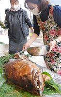 アラの姿煮を盛り付ける亀山鮮魚店の亀山弘美さん(右)=唐津市中町