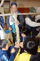 干拓老人クラブメンバーの助けを借りながら、しめ縄を作る子どもたち=白石町の有明東小学校