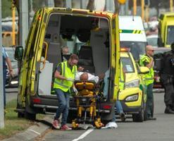 15日、銃乱射事件の現場から搬送される負傷者=ニュージーランド・クライストチャーチ(ロイター=共同)