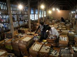 積み重ねられた木箱を動かしながら〝お宝〟を探す来客=西松浦郡有田町の幸楽窯