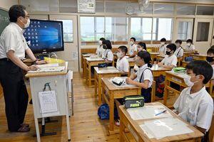 大隈知彦論説委員長(左)の話を聞く児童たち=佐賀市の金立小