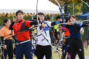 真剣に的をみつめる選手たち=佐賀市の森林公園洋弓場