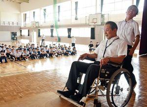 車いすの扱い方を体験する生徒(右)=吉野ヶ里町の東脊振中