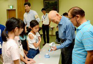 子どもたちの作品を手にする井上萬二さん(右から2人目)=有田町生涯学習センター