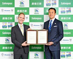 シェーン・クレイダー氏(左)から認定証を受け取った中冨社長=東京都の久光製薬東京本社