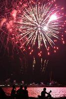 赤い打ち上げ花火が海面を鮮やかに染める=西の浜から撮影