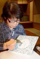 会場では伝統工芸士による実演も。だみ筆を使い下絵を描く青木妙子さん=有田町の県立九州陶磁文化館