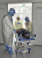 新型コロナウイルスによる肺炎患者への対応を想定し長崎大病院で行われた訓練で、患者を病室に運ぶ医師ら=28日午後、長崎市