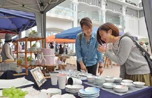 焼き物や手作り雑貨が並ぶ会場で品定めする来場者=有田町の辟アの博記念堂