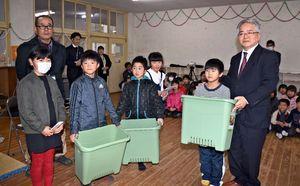 益田雄治西九州事業部長(右)からプランターなどを受け取る武雄児童クラブの子どもたち