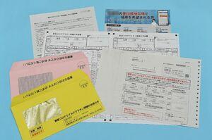 新型コロナウイルスワクチンの接種券(右手前)や予診票(中央)など。自治体から封書で届く