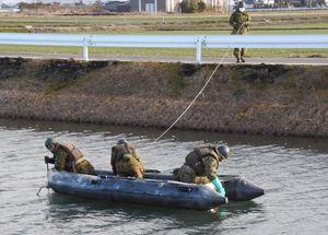 陸上自衛隊ヘリコプターの墜落現場近くの水路で、部品が沈んでいないか、ボートで捜索する自衛隊員=11日午前9時ごろ、神埼市千代田町