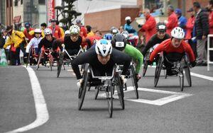 伊万里ハーフマラソン大会で新設された3キロ車いすの部をスタートする選手=伊万里市伊万里町