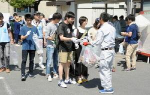 集めたゴミを市職員に手渡す清掃活動の参加者=佐賀市役所横駐車場