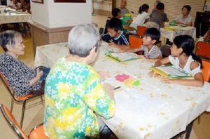 養護老人ホームとケアハウスを利用するお年寄りから戦争時の話を聞く塩田小3年の子どもたち=嬉野市の済昭園