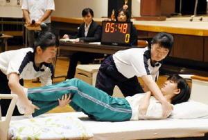 介護技術コンテストで、ベッドへの移乗を介助する高校生=神埼市中央公民館