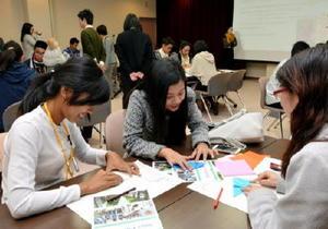 大学生(右)の指導を受けながら折り鶴を作る高校生=佐賀市の佐賀大学本庄キャンパス