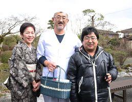 生徒から手作りのかごを受け取り、笑顔を見せる古賀義紹さん(中央)と悦子さん(左)=神埼市神埼町の味膳「古雅味」