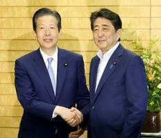 会談前に握手する安倍首相(右)と公明党の山口代表=22日午後、首相官邸