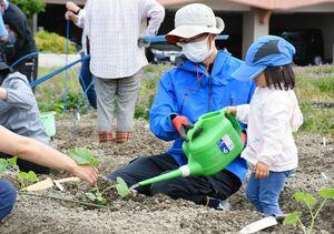 植えた野菜の苗に水をやる親子=佐賀市神野西