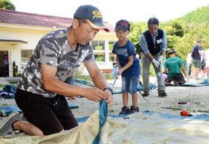 協力しながらテントを組む父親と子ども=嬉野市の「分校cafe haruhi」