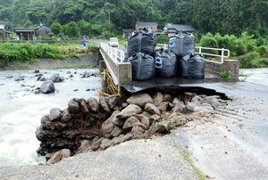 記録的な大雨で、橋のたもとが大きくえぐり取られ、通行不能になった上古枝橋。浜川に架かる橋で、左側が上流=7日午前11時ごろ、鹿島市古枝(撮影・中島幸毅)