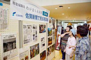 玄海町の歴史を振り返る佐賀新聞の紙面や写真に見入る見物客たち=玄海海上温泉パレア