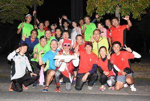 還暦を迎えた日に60周を完走した杉原和嘉さん(前列左から3番目)。多くのランニング仲間が祝福した=佐賀市の県総合運動場