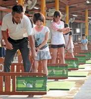 プロの指導を受けながらスイングの方法を学ぶ子どもたち=吉野ヶ里町のゴルフガーデン三田川