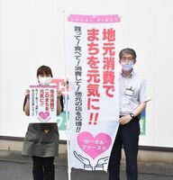地元消費を呼び掛けるのぼり旗とポスターを発案した早田文昭さん(右)=伊万里市二里町