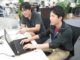 インターンシップに参加した大学生(右)に、プログラム開発を指導するエンジニア=7月下旬、オプティム東京本社