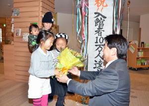 10万人目の入館者となった平川さん(左)に松田町長から花束と記念品が贈られた=基山町立図書館