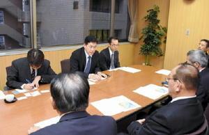 JAさがの金原壽秀組合長(手前左から2人目)らにオスプレイの佐賀空港配備計画の概要について説明する九州防衛局の市川道夫企画部長(奥左から2人目)=佐賀市のJAさが本所