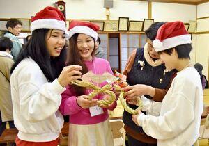 クリスマス会で、興味深そうにしめ縄作りに取り組むベトナムからの実習生ら=神埼市の姉集落センター