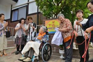 交流館「エミコ オハナ」オープンに先立つ開設式典に参加した小野恵美子さん(中央)=6月、福島県いわき市