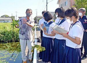 ため池に茂るヒシについて説明する本村宣行神埼和菱組合長(左)=神埼市神埼町