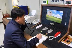 再開した南北間直通電話で北朝鮮側と通話する韓国の担当者=3日、板門店(韓国統一省提供・共同)