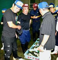 フグの初競りで「袋競り」をする仲買人(左端)と競り人(左から2人目)=21日未明、山口県下関市の南風泊市場