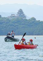 唐津城を望む海上で、シーカヤックを楽しむ子どもたち=唐津市二タ子の県ヨットハーバー