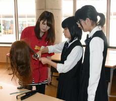 広告の着想を得ようと、ヘアアレンジの授業を体験する生徒=佐賀市の佐賀女子高校