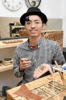 作品のクモを手にする伊藤尚史さん=鳥栖市本町のいとお眼鏡・時計店