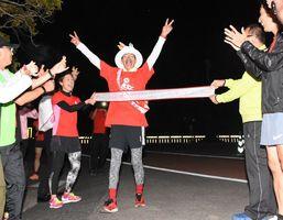 還暦を迎えた日に60周を走り抜き、ゴールテープを切る杉原和嘉さん=佐賀市の県総合運動場