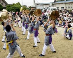 祭りの呼び名の由来になった鉦風流。重さ16キロの大鉦を片手で持ち上げ、舞い鳴らす=基山町の老人憩いの家前
