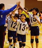 ビギナーの部で優勝を決め、笑顔でハイタッチする「TeamSashiMe。」の選手たち=佐賀市の諸富文化体育館