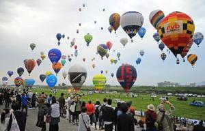 多くの来場者が見守る中、熱気球世界選手権で大空へ一斉に飛び立つバルーン=10月31日、佐賀市の嘉瀬川河川敷