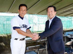 激励に訪れた門田豊会長(右)と佐賀商の森田剛史監督=佐賀市の同校グラウンド