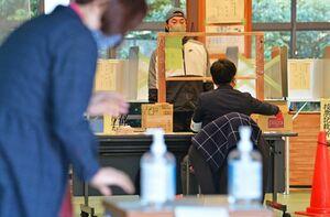 唐津市長選・市議選で、出入り口に手指消毒液を置き、投票用紙の受け取りなどの手続きをフィルム越しに実施した投票所=31日午後、唐津市浜玉町のひれふりランド