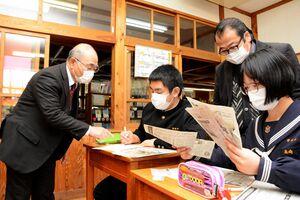 新聞記事から各国の感染状況や政府の対応を探る生徒ら=神埼市の脊振中