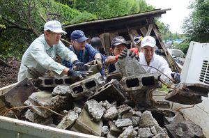 道端に散らばったブロック塀の破片など拾い集め、軽トラックに積み込むボランティア=6月26日、熊本県西原村