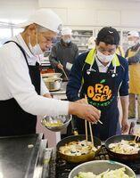 岩永章一郎さん(左)の助言を受け、皿うどんを作る教室参加者ら=太良町のしおさい館